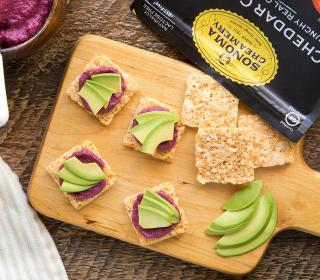 Sonoma Creamery Cheese Snacks topped with beet hummus and avocado slices