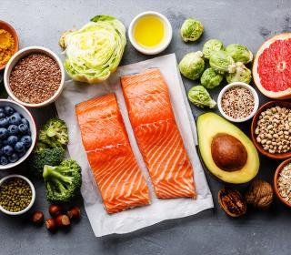 An array of healthy foods, including salmon, avocado, nuts, fruit, whole grains and olive oil