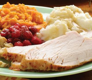 Slices of roast turkey breast served with mashed potatoes with gravy, sweet potatoes, cranberries, and stuffing