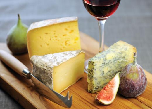Cheese board with cheese, figs and a glass or red wine