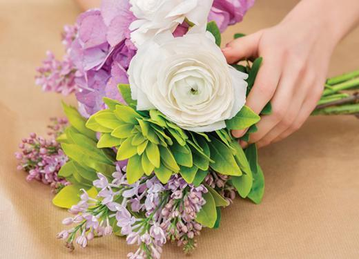 A woman preparing to wrap up a fresh bouquet of flowers with craft paper