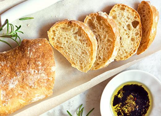 Fresh baked ciabatta bread sliced and served on a white plate with a bowl of herbed olive oil for dipping