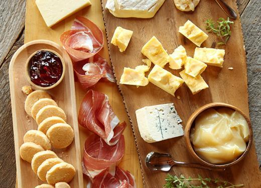 A wooden cheese board featuring Bent River Camembert, Milton Creamery Prairie Breeze Cheddar, Northern Lights Blue, Sartori BellaVitano Gold, Lucille's Red Pepper Jam, Velvet Bees Honey Butter, La Quercia Prosciutto and A Gourmet Thyme Cayenne Shortbreads