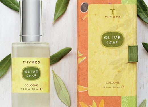 A top-down photo of a bottle of Thymes Olive Leaf Scented Cologne set atop a white wooden table with real olive leaves scattered around it
