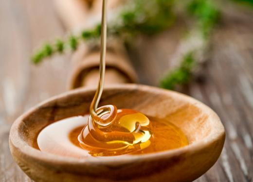 Bright gold honey being drizzled into a wooden spoon