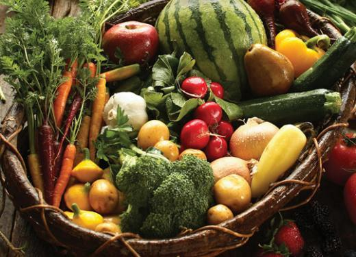 A large basket filled with assorted fresh fresh fruits and vegetables from the garden