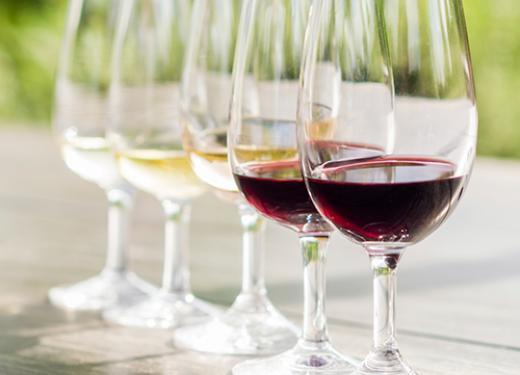 A line of wine glasses from a wine tasting flight, ranging from sweet white to full-bodied red