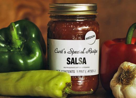 A jar of Curt's Special Recipe Salsa with fresh bell peppers, jalapeño, and garlic