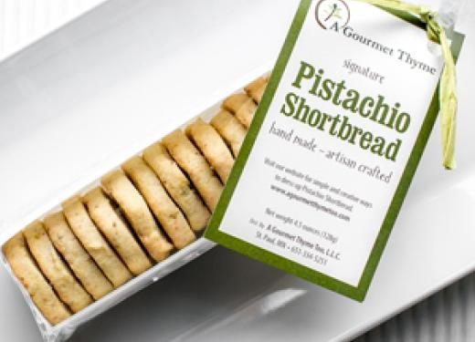 A package of A Gourmet Thyme Too Pistachio Shortbread on a white plate