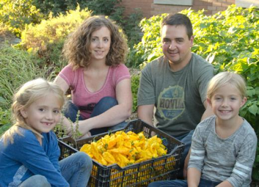 Troy, Leslie, and their two young daughters posing with a large woven basket filled with fresh-picked hot peppers in their backyard garden