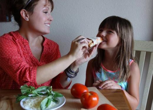 Christine Stoen playfully feeding her daughter, Gracie, a slice of pizza made from Mama Stoen's gluten-free baking mixes