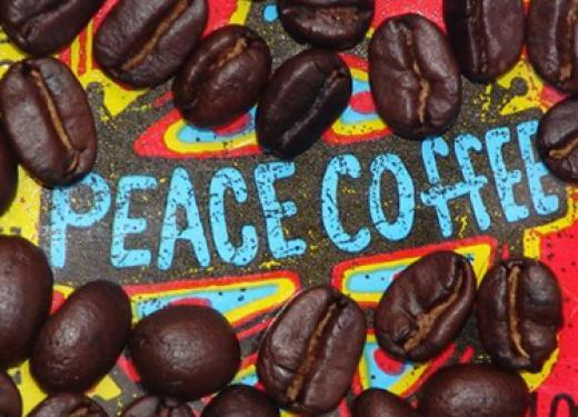 Closeup of a Peace Coffee bag framed by roasted coffee beans