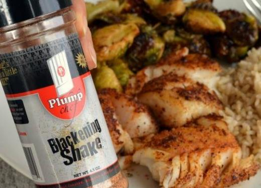 Plump Chef Blackening Shake Seasoning next to a plate of baked fish, brown rice and Brussels sprouts