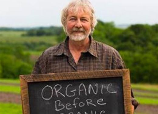 "Peter Gengler standing in his farm field holding a chalkboard with these words written in white chalk: ""Organic Before Organic Was Cool"""