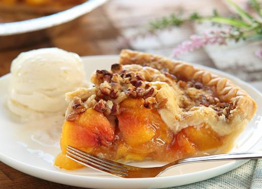 A slice of Kowalski's Signature Peach Pie served with a scoop of vanilla ice cream