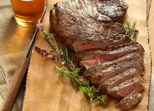 Cooked steak sliced on a wooden cutting board next to a tall glass of beer