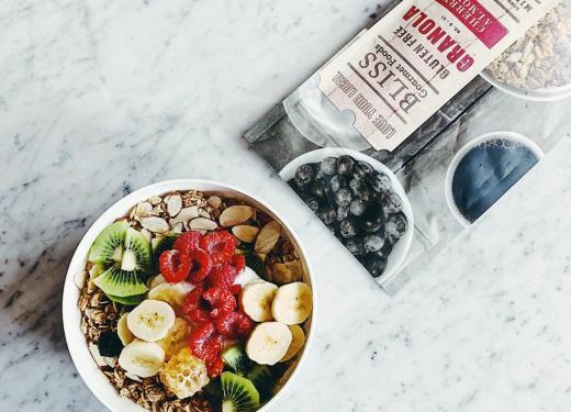 A package of Bliss Cherry Almond Granola next to an artfully styled granola bowl with fresh raspberries, banana, and kiwi