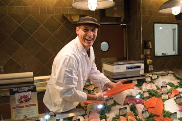 Woodbury Seafood Manager Darryl holding up a fresh fillet of salmon at the Seafood counter