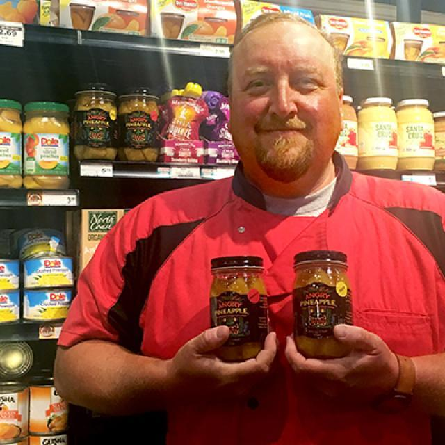 Founder Rob Burke holding a jar of Angry Pineapple in the Kowalski's grocery aisle