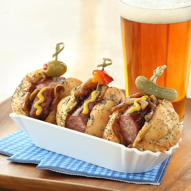 Three Big Steer Sausages, each served in a sesame seed bun with mustard, bacon, cheese, and a cornichon for garnish