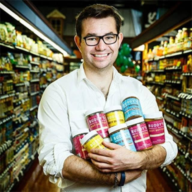 Buddy's Nut Butters founder Andrew Kincheloe holding an armful of his nut butters in the Kowalski's grocery aisle