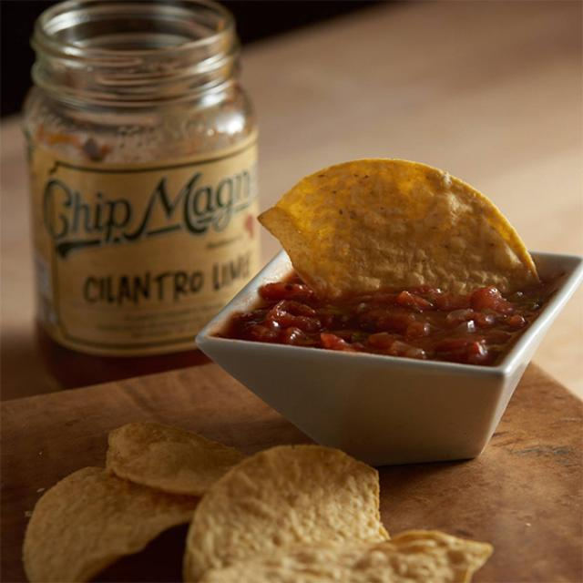 A jar of Cilantro Lime Chip Magnet Dip served with yellow corn tortilla chips