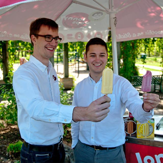 The founders of Jonny Pops holding up their frozen fruit bars next to their food cart