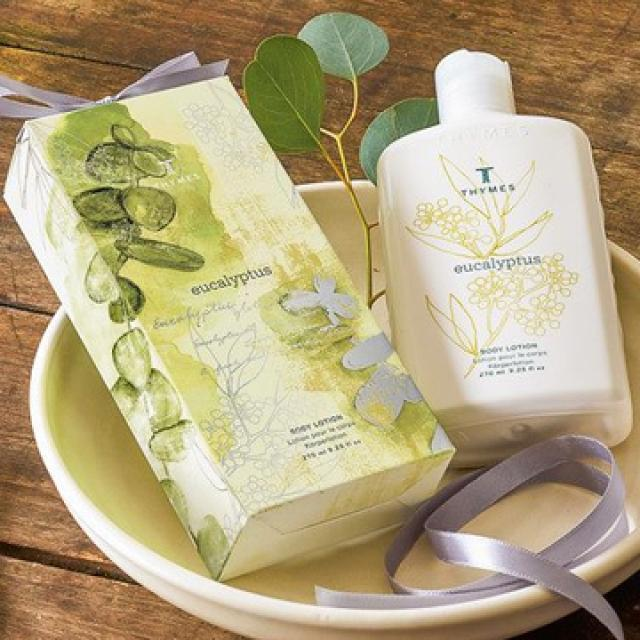 A bottle of Thymes Eucalyptus Body Lotion on a wooden table with a fresh eucalyptus leaf