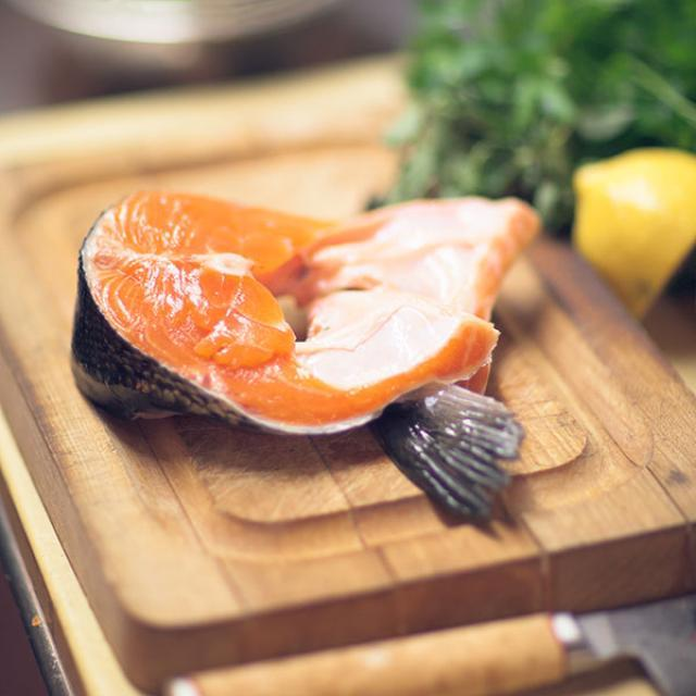 Fresh Skuna Bay salmon fillet on a wooden cutting board with a lemon half and fresh parsley