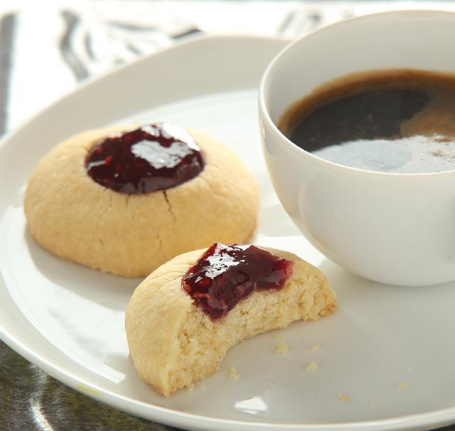 Thumbprint cookies filled with raspberry jam next to a cup of hot cocoa