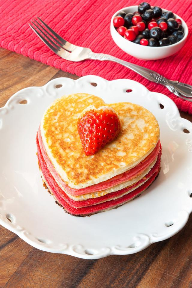 A stack of heart-shaped pancakes with berries on top