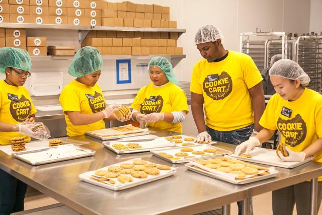 Five teenagers wearing hair nets, gloves and bright yellow Cookie Cart shirts collect fresh-baked cookies from baking sheets
