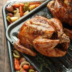 Whole roasted chicken on a roasting pan with carrots, potatoes, celery and onions